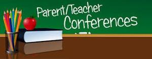 Chalkboard that says parent/teacher conferences behind a desk with a book and pencils