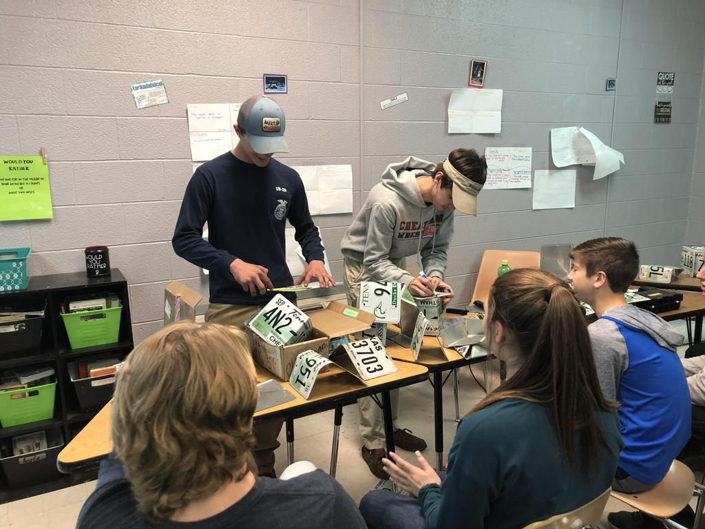 High school students show how to make birdhouses from license plates