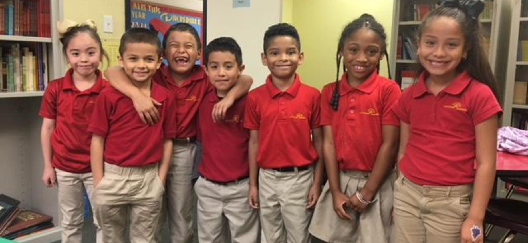 Elementary students in red polo uniform shirts