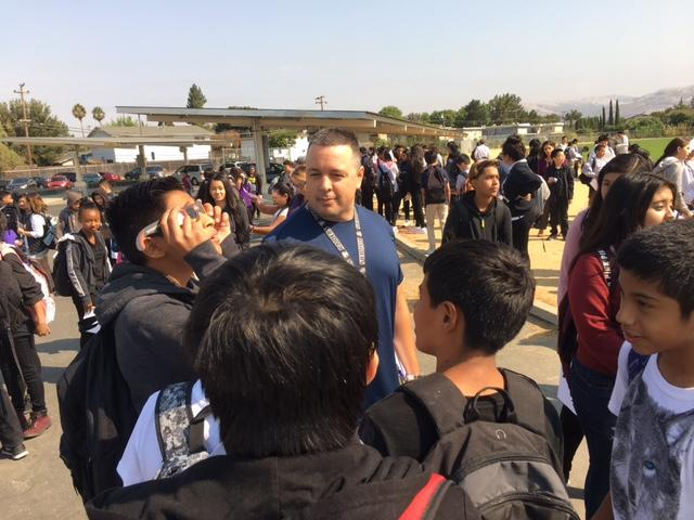 student looks at solar eclipse through safely glasses while surrounded by several students and a teacher