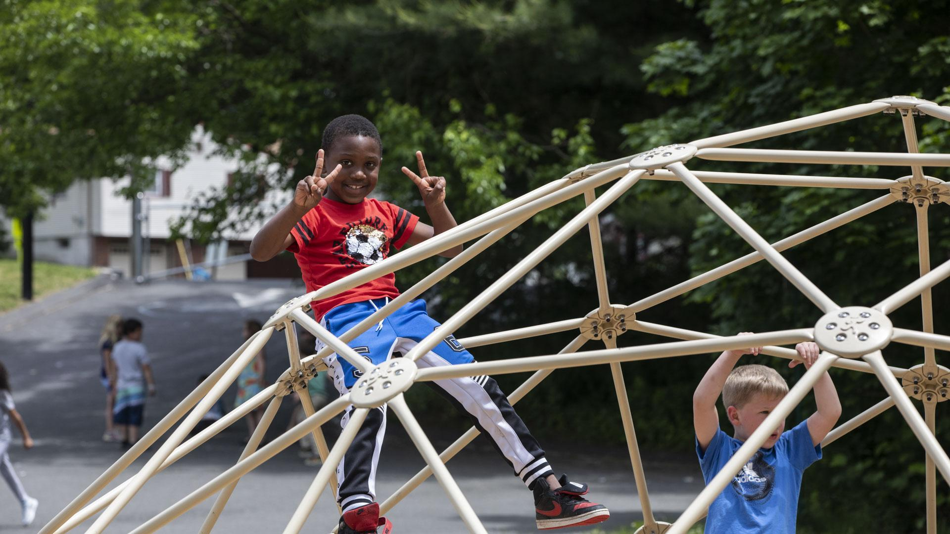 Two boys climbing on playground equipment