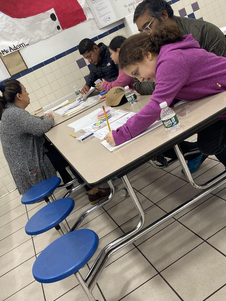 a girl and her dad solving the math problem at a table with another family