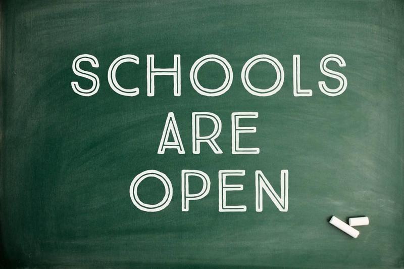Schools are Open written on a green chalkboard