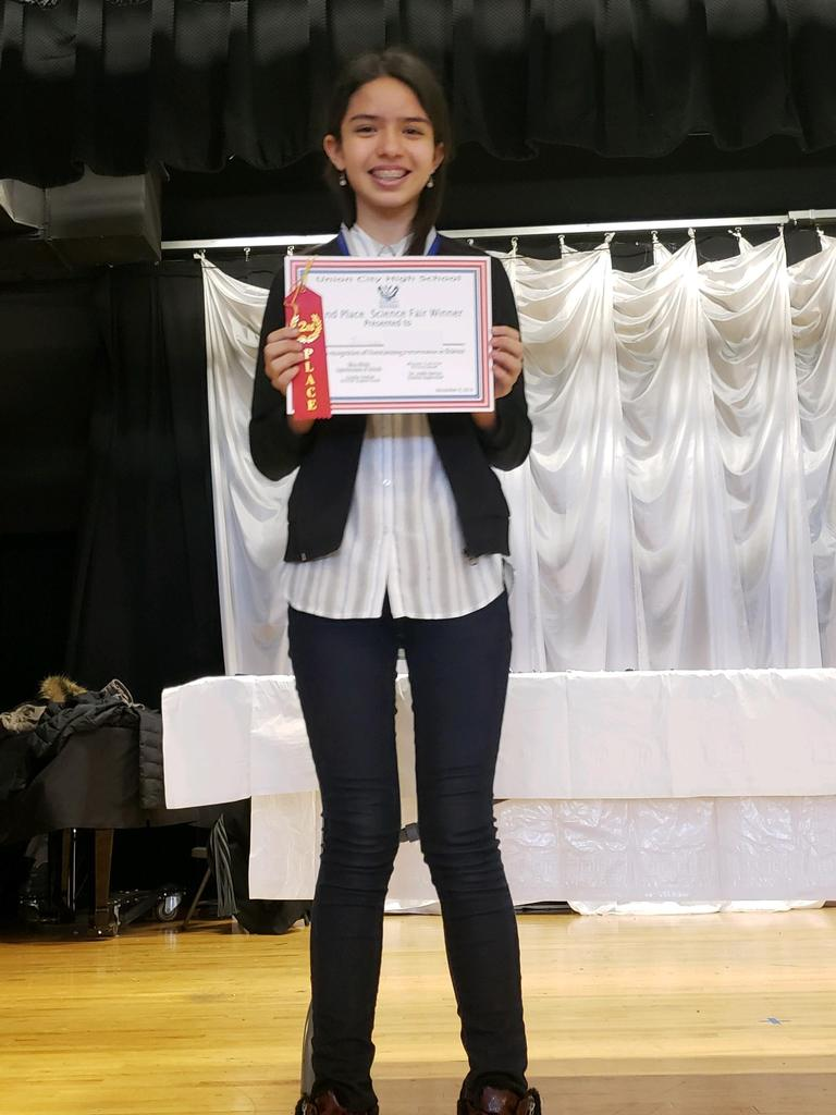 uhms female student holding her first place certificate on stage