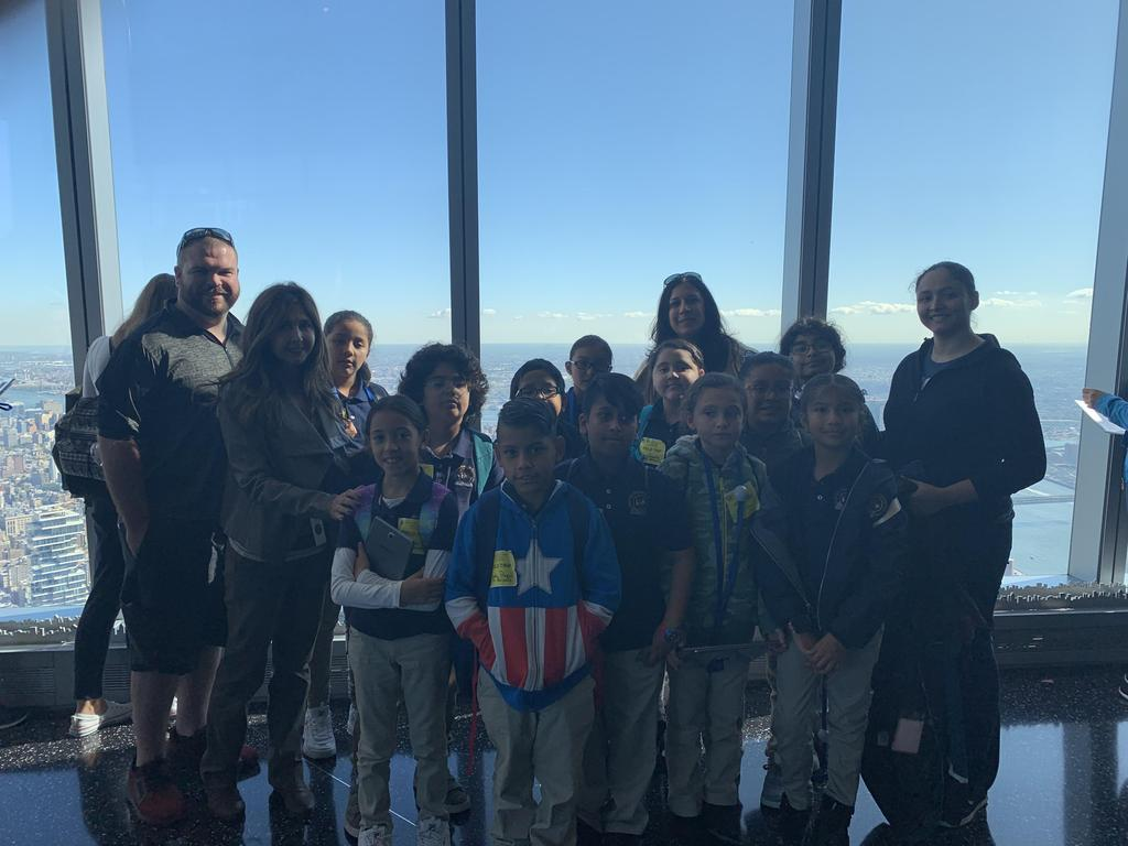 Mr. Blake, Marinello, Ms. Logothetis, & Ms. Cintron and several students standing in front of the window with the NYC background