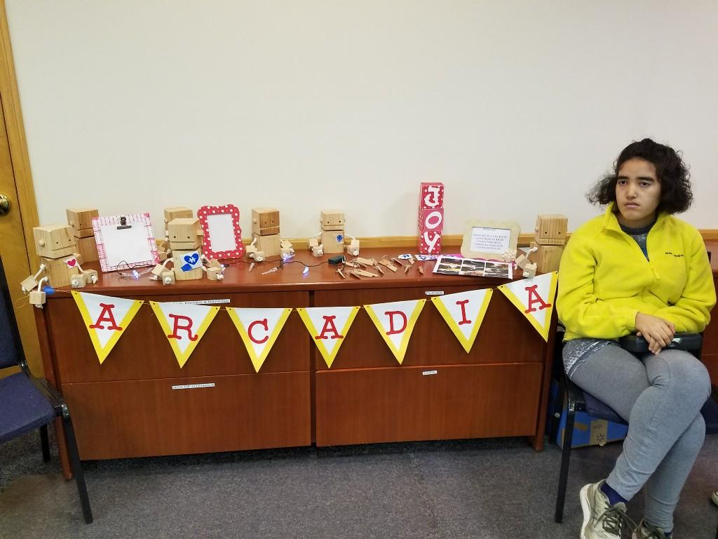 Student sitting at table selling crafts
