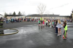 Fire department spraying students with water