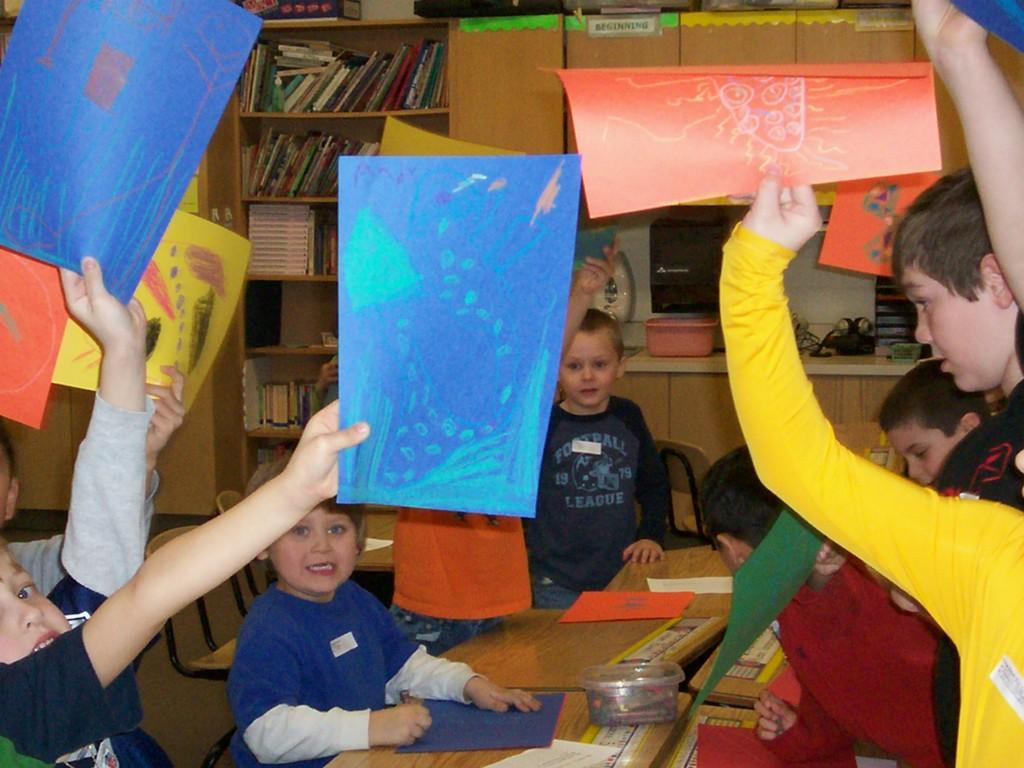 students hold up art projects