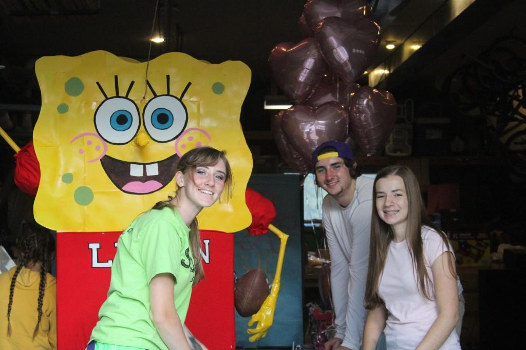Three students in front of a parade float with Sponge Bob
