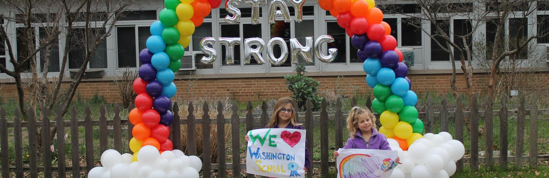 Photo of Washington School students holding signs in front of rainbow made of balloons.