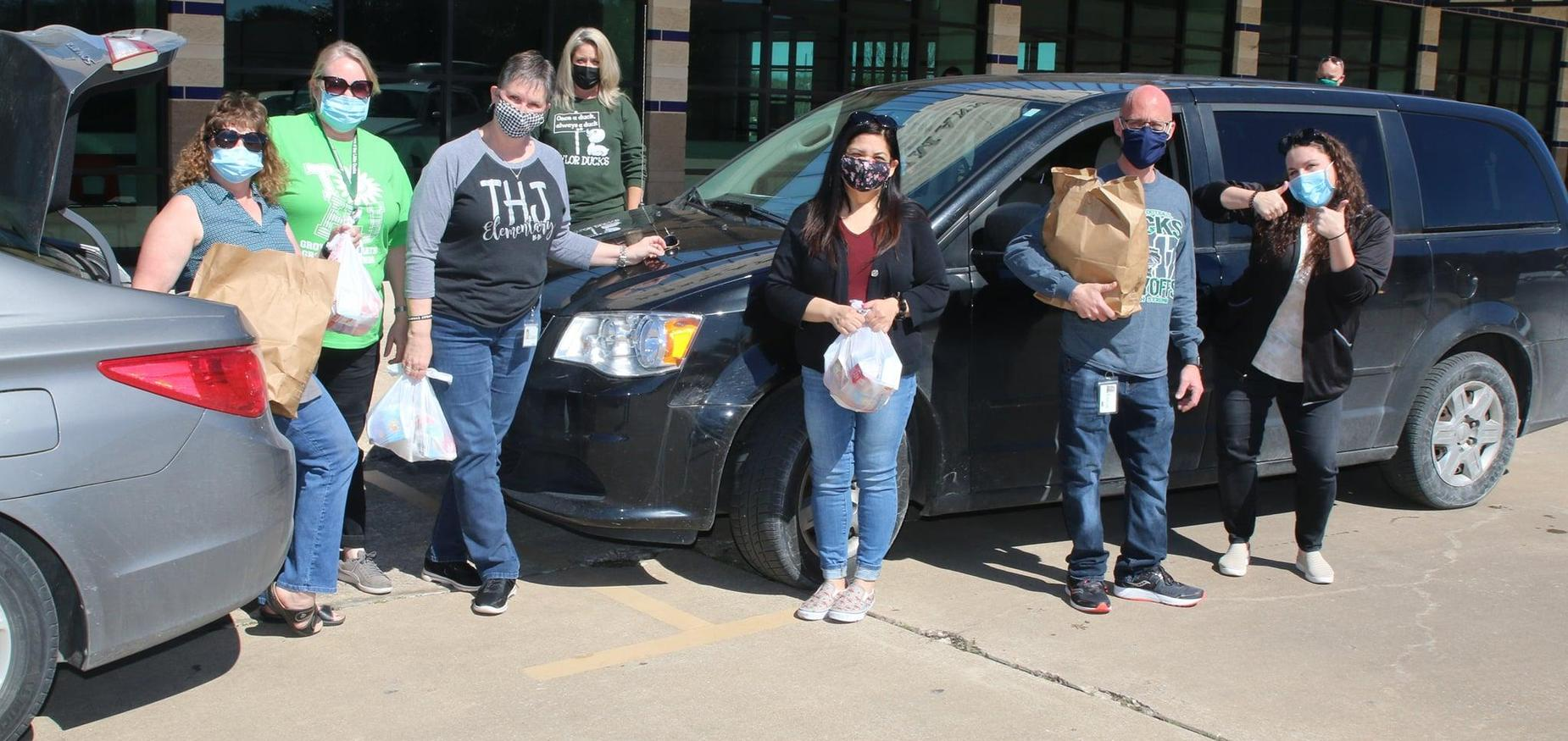 staff help deliver meals to students