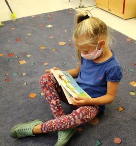 Photo of kindergartner reading a book