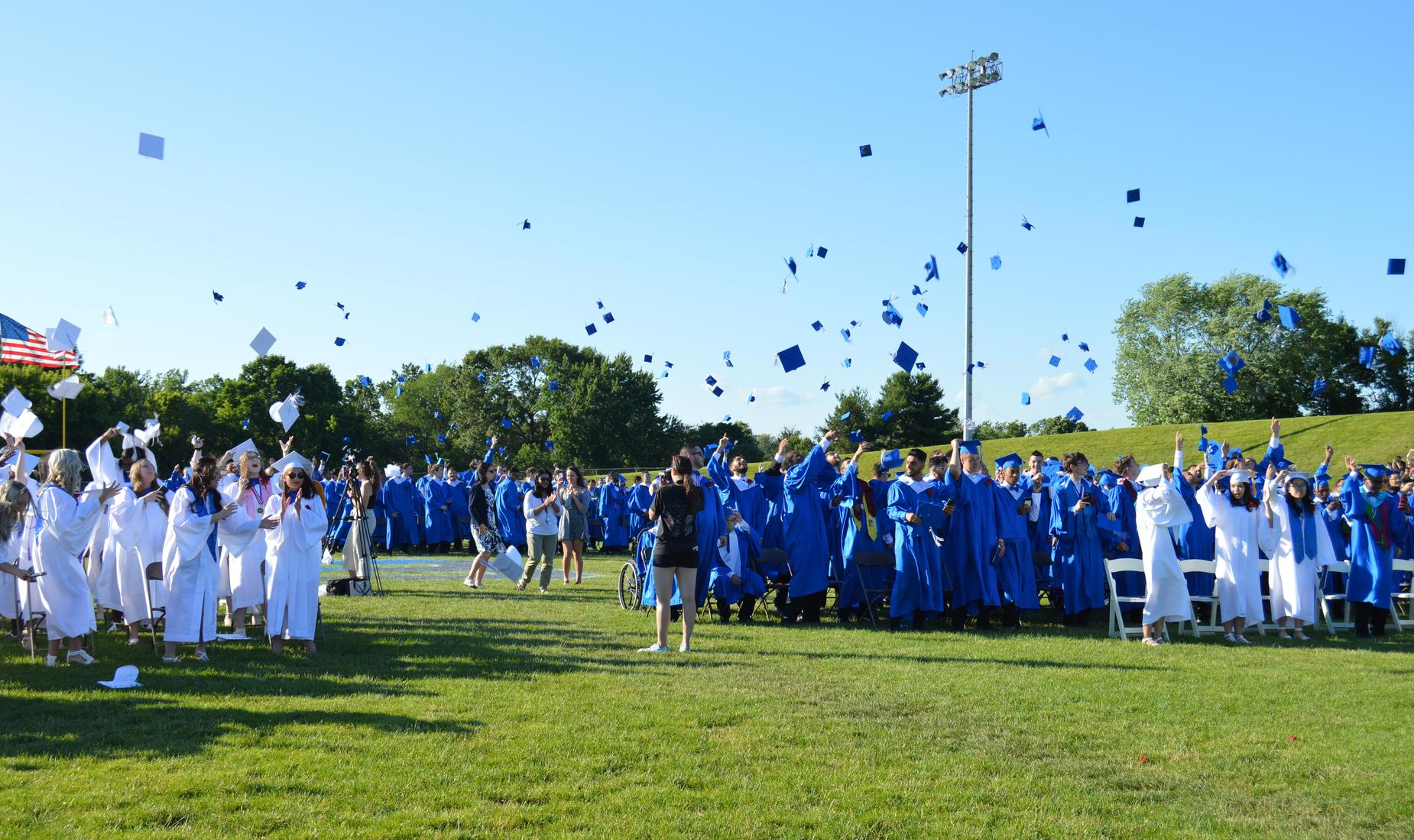 Class of 2019 graduates, in white and royal blue gowns, toss their caps in the air
