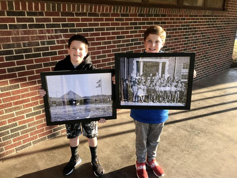 Two students holding up pictures of Travis Elementary