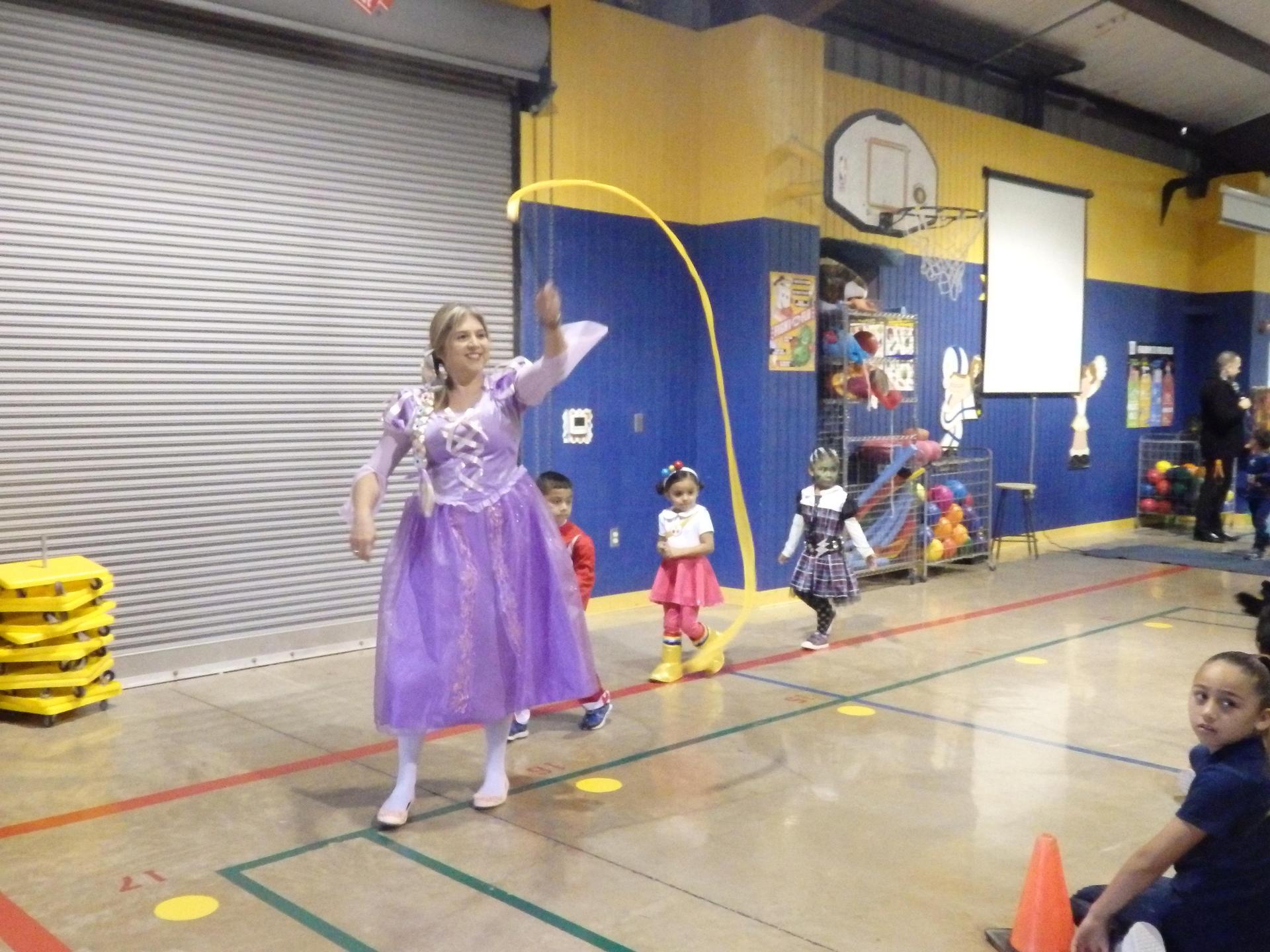 PK teacher walks with her students in halloween parade.