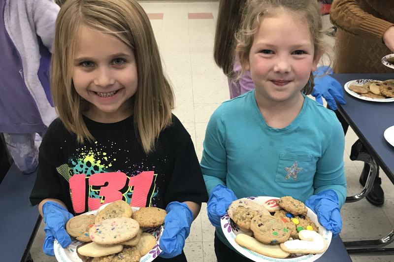Two Alamo students hold plates of cookies.