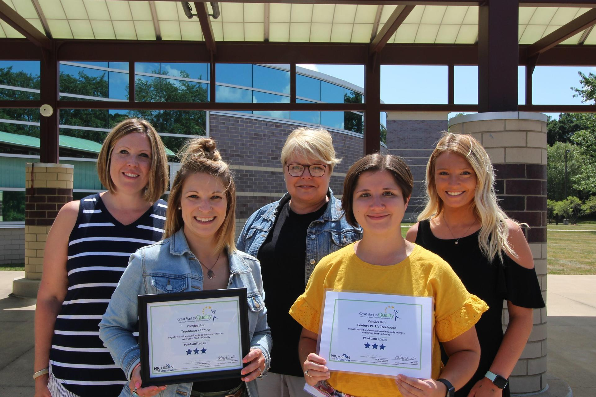 5 ladies outside of the school hold their certificates