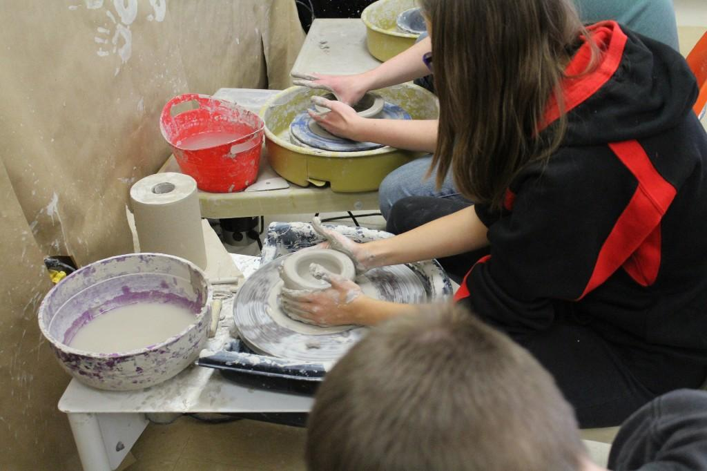 Students creating pottery on a pottery wheel
