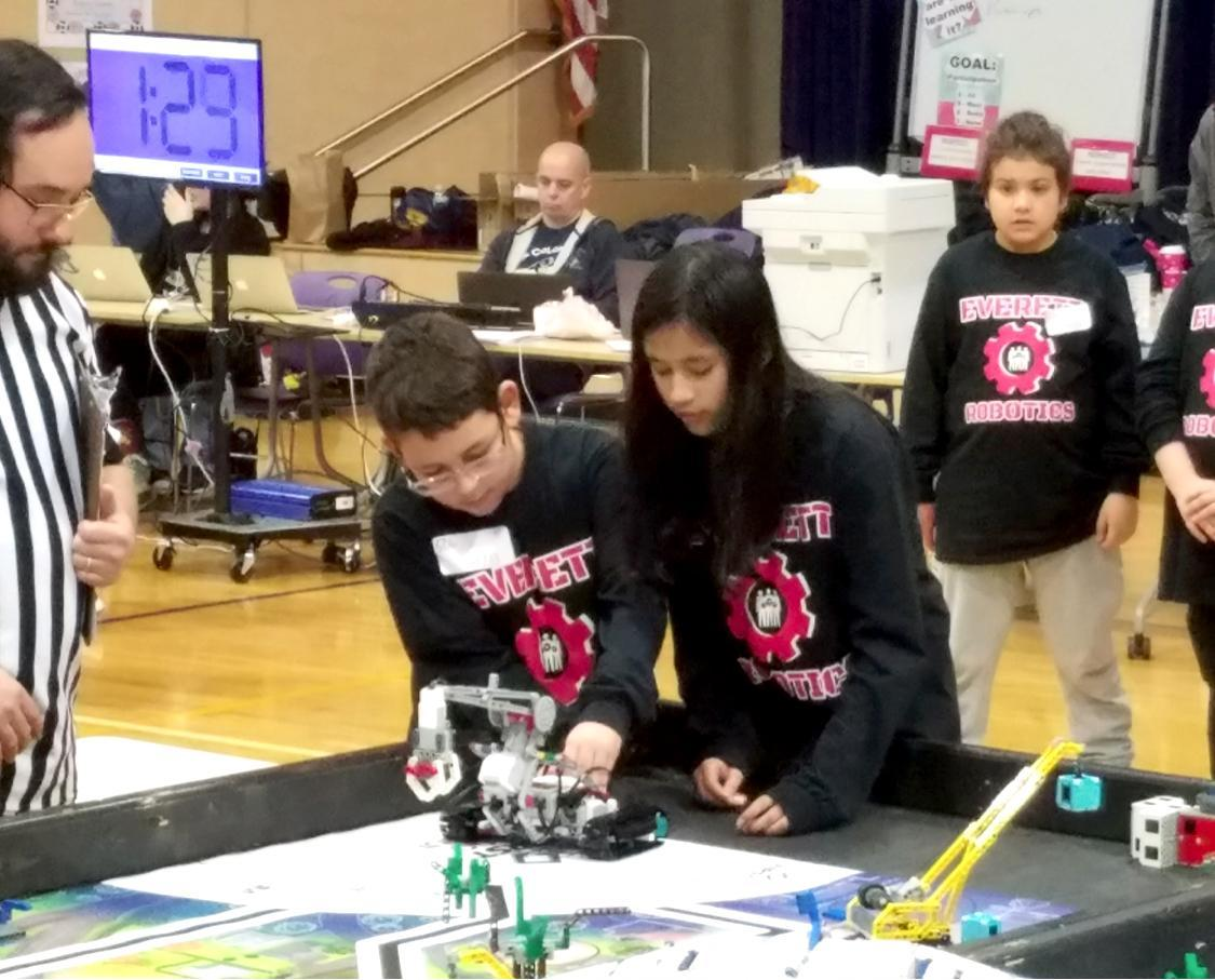 Two students lean over a table and make adjustments to their robotics device as a referee looks on