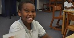 Fourth grade student sitting at a table smiling.
