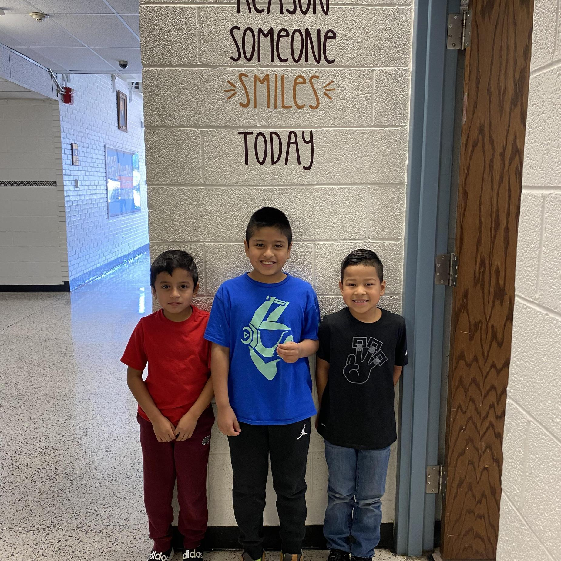 A group of three students smiling.