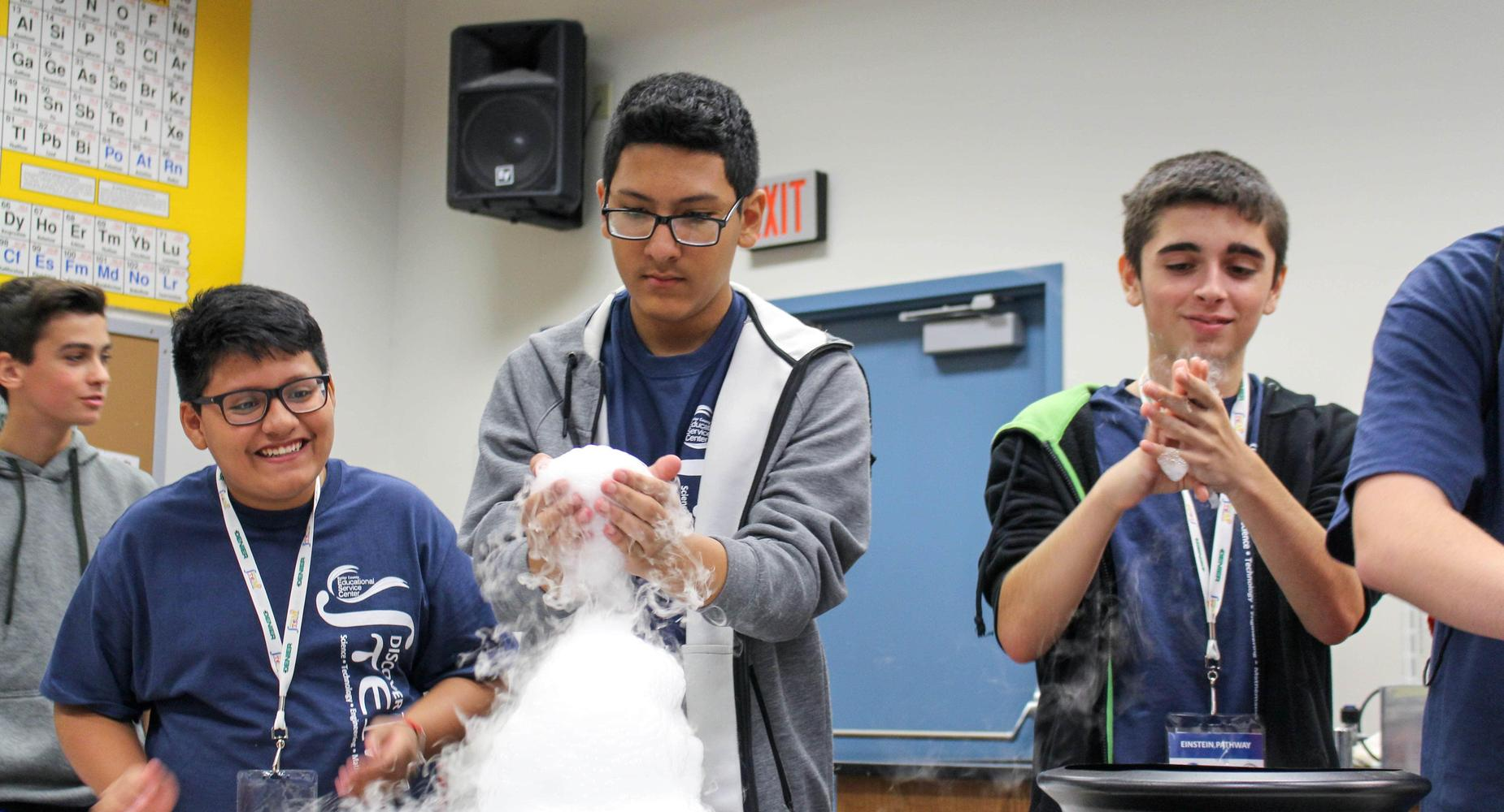 Three male middle school students play with artificial clouds at the Discover STEM Conference hosted by Miami University Regionals