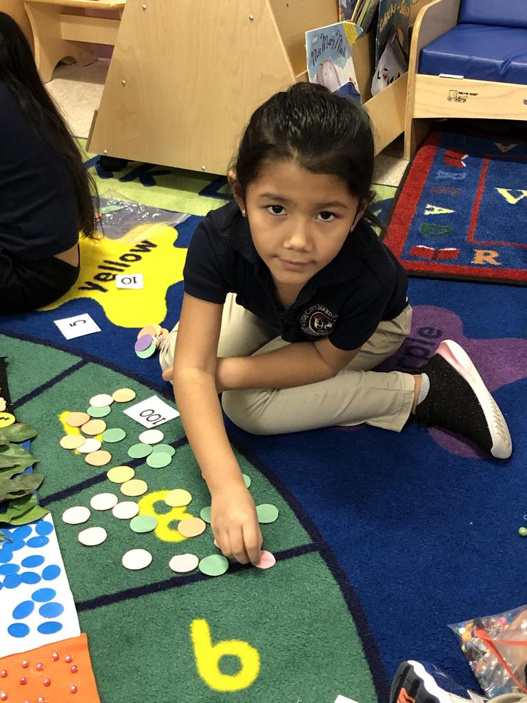 close up of girl placing a circle on the 100 days of school banner
