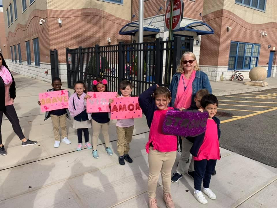 several kids lined up holding breast cancer awareness posters