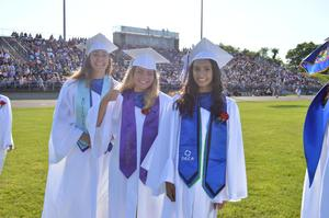 3 seniors pose for a picture.  They were lined up waiting to receive their diploma