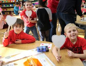 Photo of three students at McKinley School enjoying Valentine's Day activities.