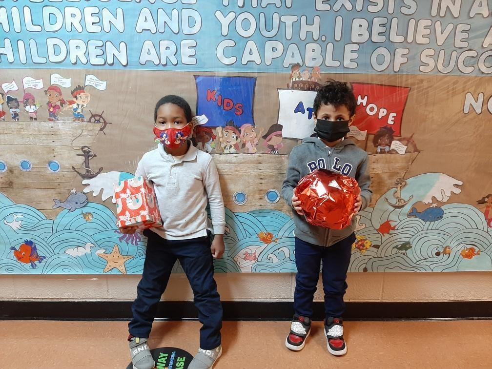 Two students posing with gifts.