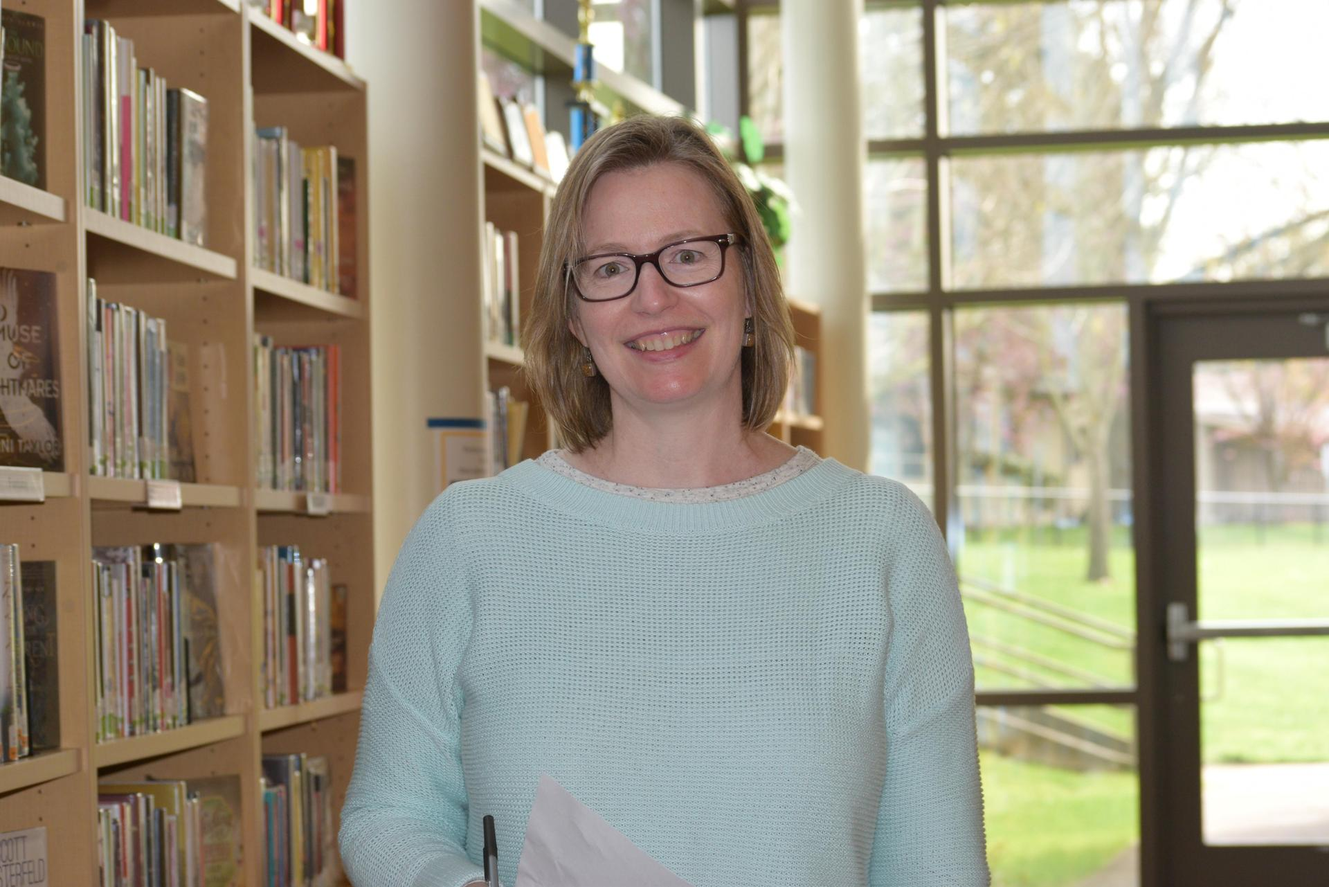 woman smiling as she stands next to shelves of books in a library