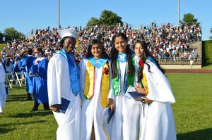 4 girls, dressed in their white gowns, pose for a photo on the field