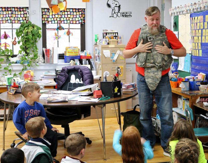 Anthony DeFoe, a 12-year veteran of the U.S. Army, speaks to 1st graders at McKinley School on Nov. 11, as his son, Quinn (left) proudly looks on.