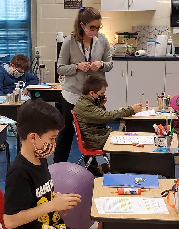 A teacher works with a student.