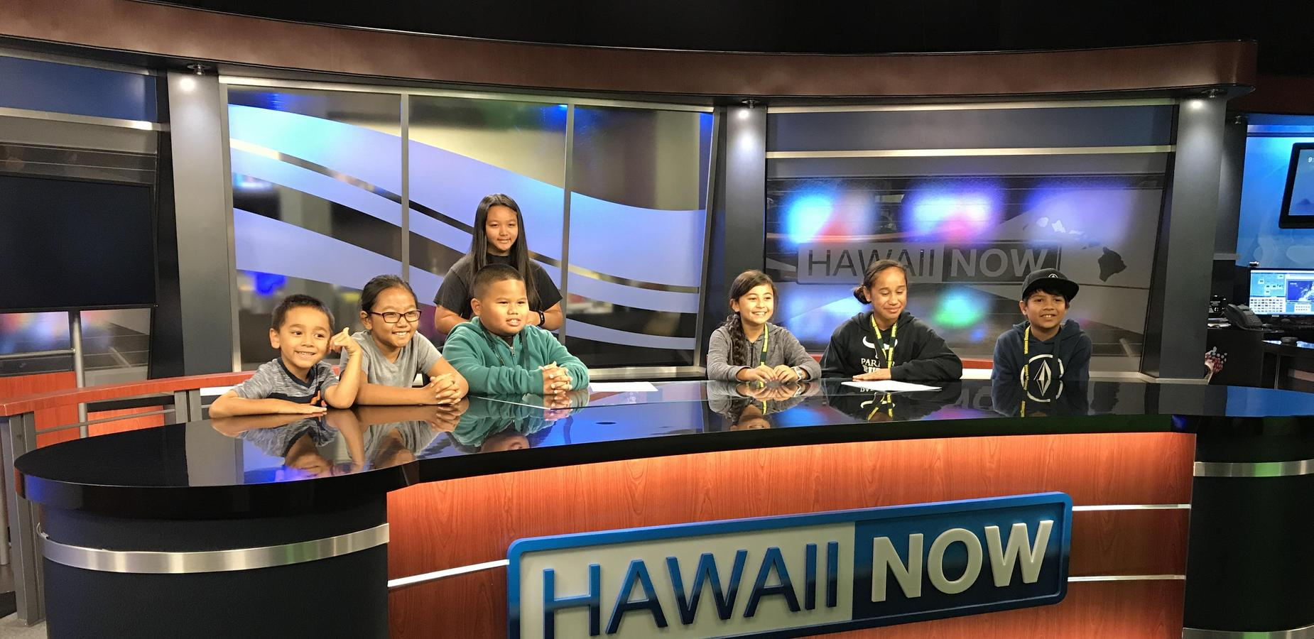 students sitting at news desk