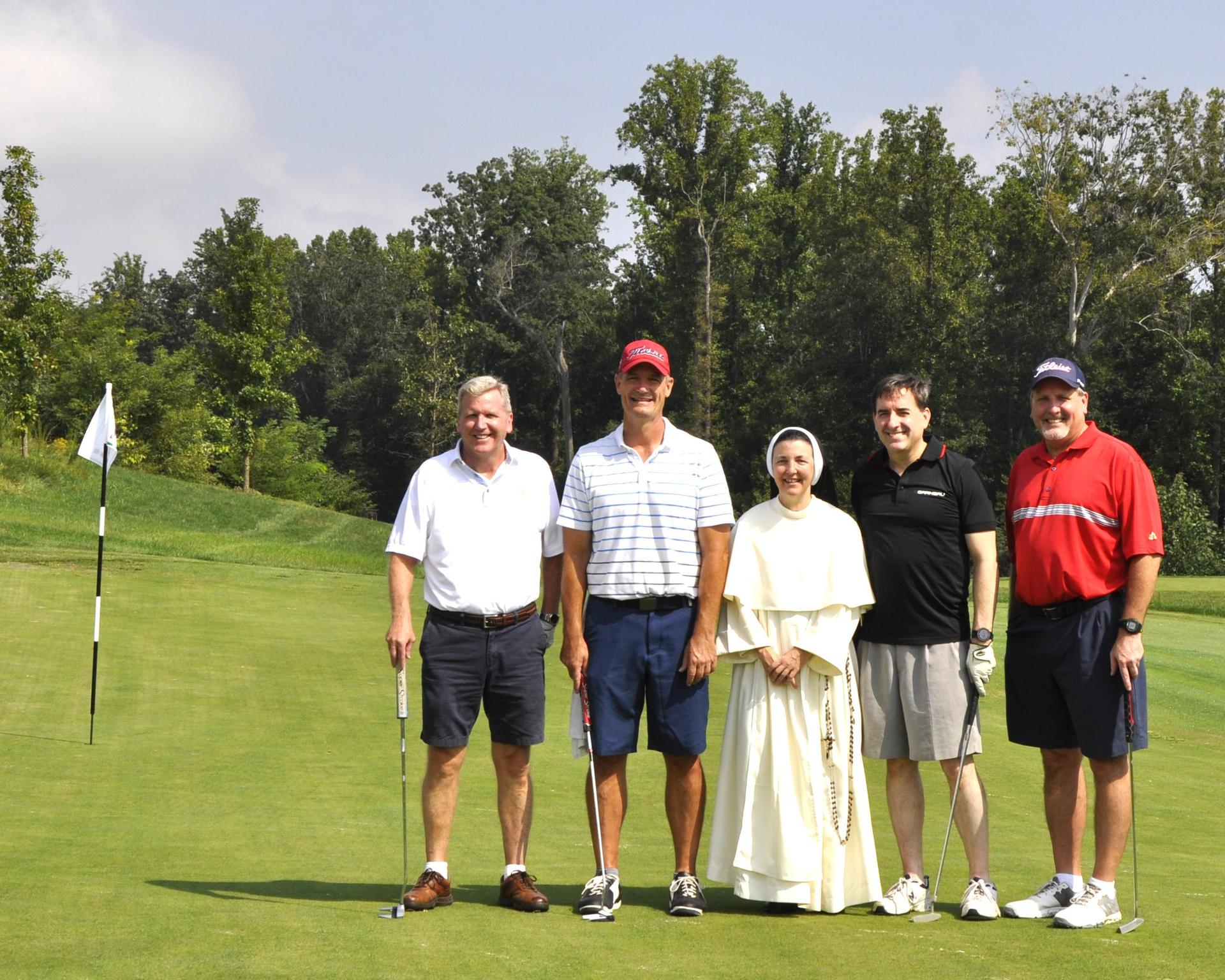 A group of golfers pose