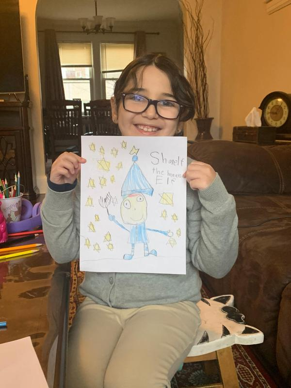 Selma holding her elf drawing