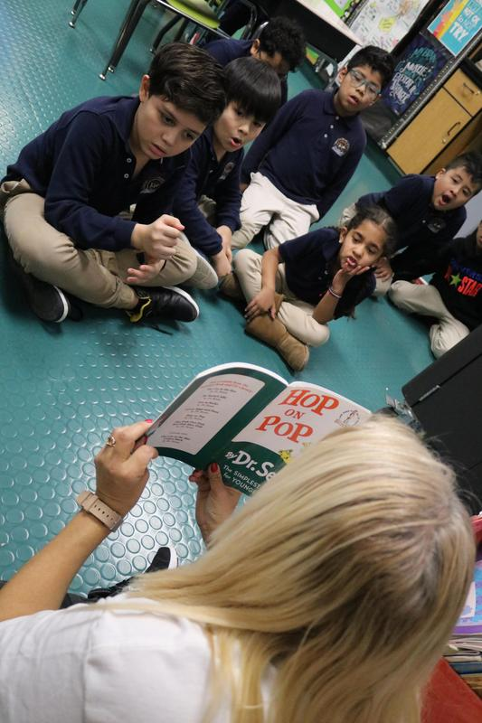 close up of little boy looking along as Ms. Bristol reads a book to the class
