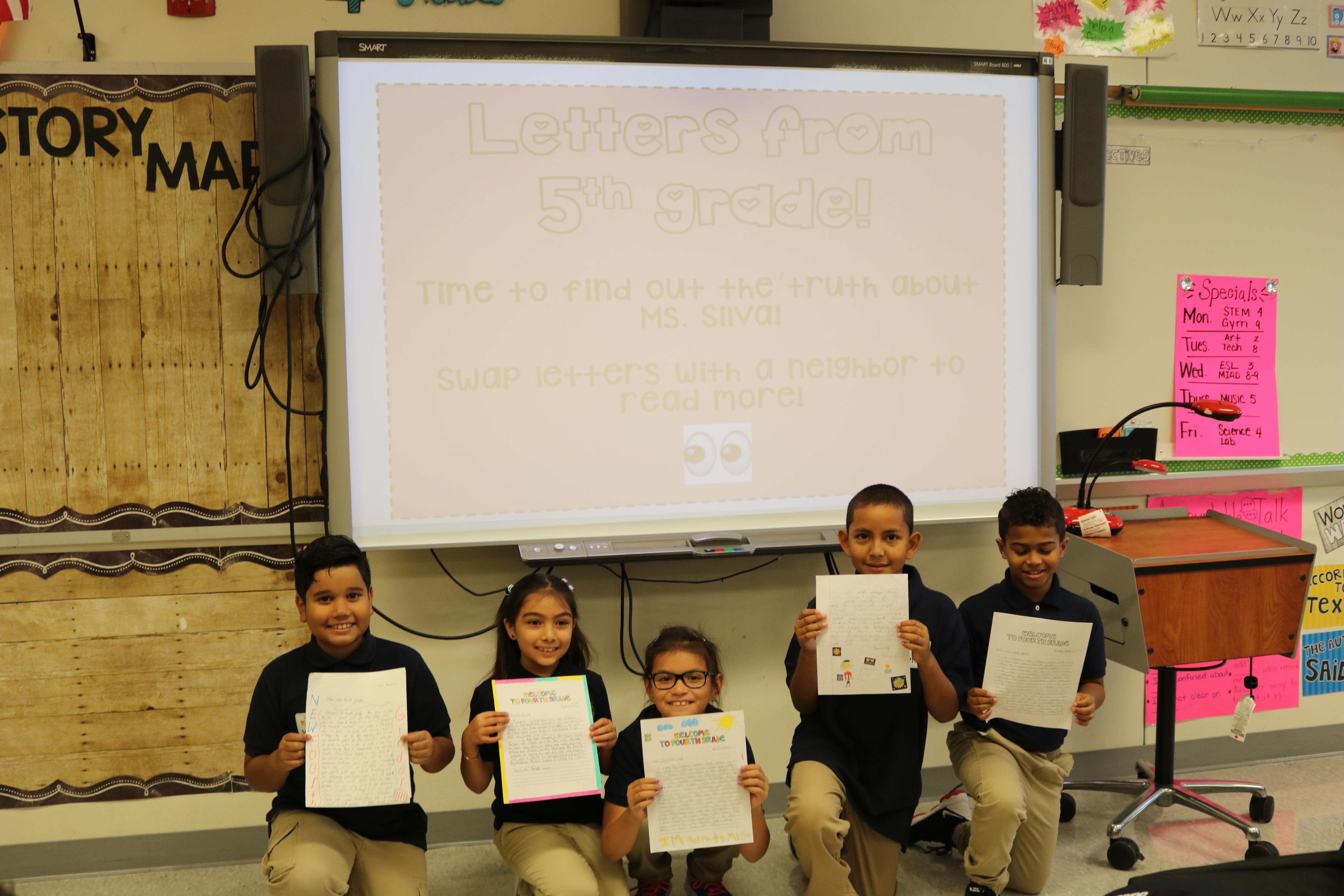 5th grade students proudly showing off their first assignments
