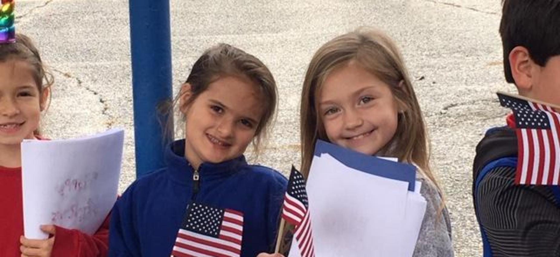Second grade students holding cards and American flags