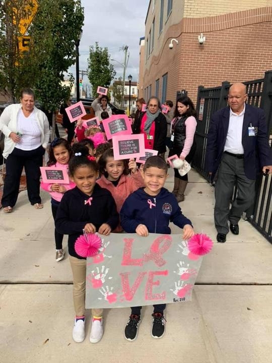 two kids leading their class with a banner that says love