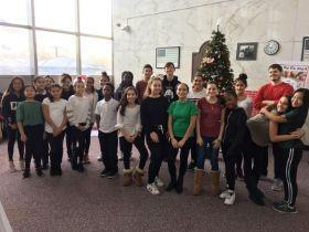 Students signing in VA hospital, there is a Christmas tree in the background.