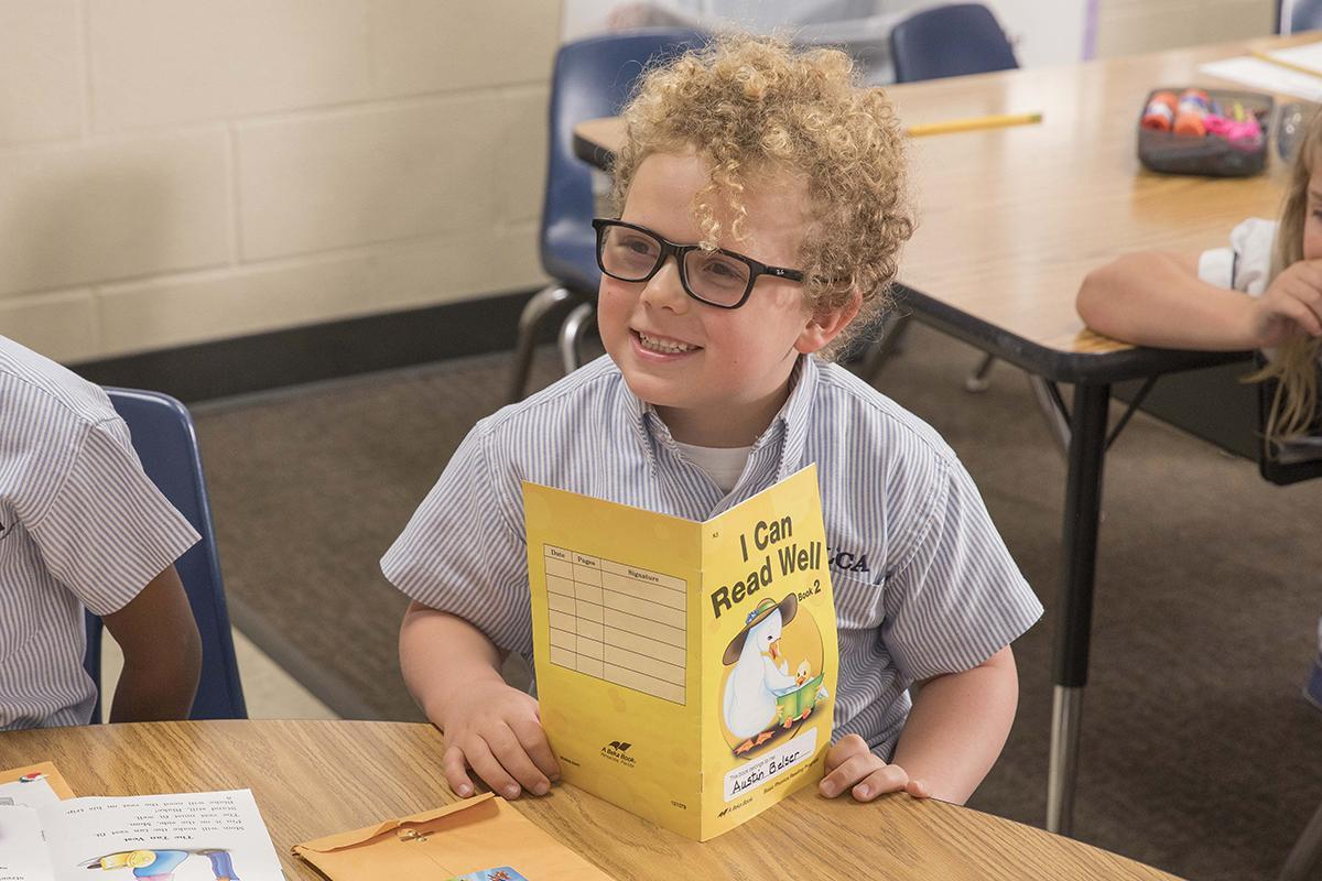 kindergarten student reading book