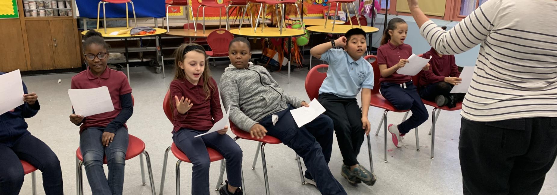 STUDENTS PRACTICING NEW MUSIC IN CHORUS PROGRAM