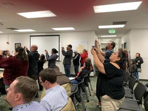 parents taking photos with cellphones of students at board meeting