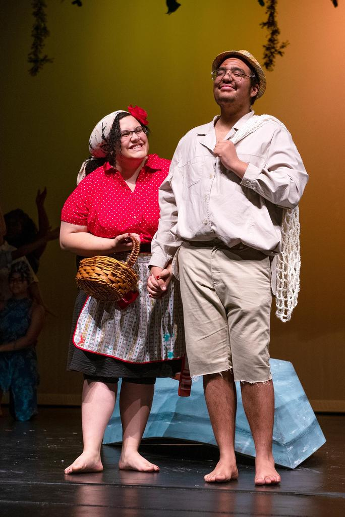 Maya Jamison Walsh, as Mama Euralie, holds a basket and smiles up at Darnell Hall, who plays Tonton Julien