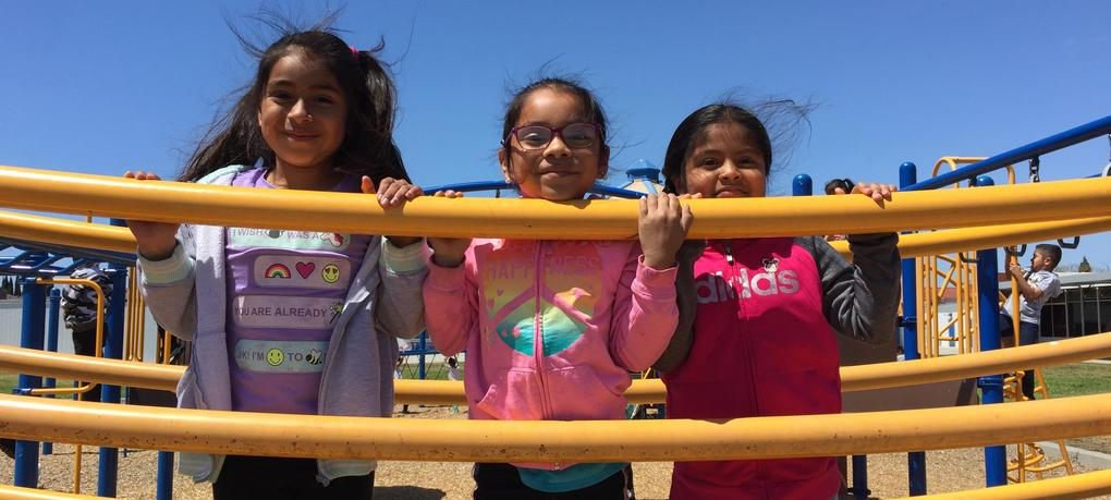 Students smile from play equipment.