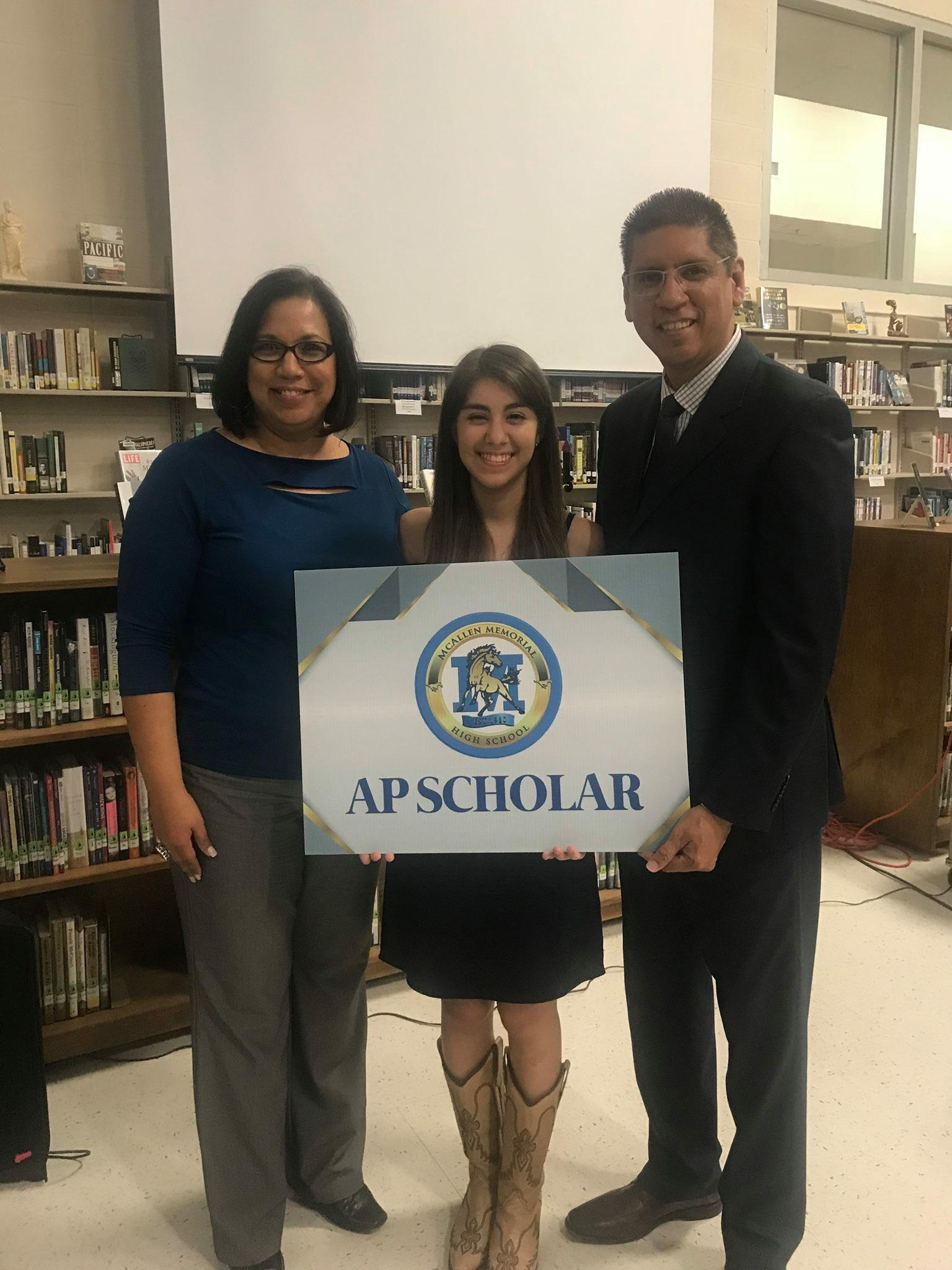 student with administrators holding AP Scholar yard sign