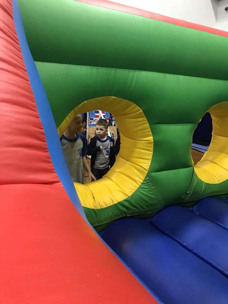 two boys looking into the obstacle bouncy house